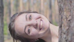 Πορτρέτο του ευτυχούς κοιτάγματος γυναικών χαμόγελου νέου από πίσω από τον κορμό δέντρων και του κρυψίματος πάλι Ενότητα με την ά απόθεμα βίντεο