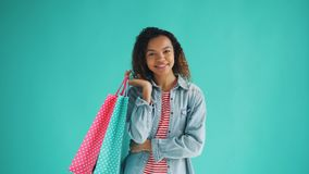 Πορτρέτο του ευτυχούς κοριτσιού αφροαμερικάνων με τον ψωνίζοντας ικανοποιώ τσάντες πελάτη φιλμ μικρού μήκους