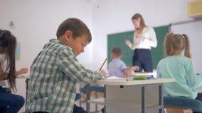 Πορτρέτο του ευτυχούς μαθητή στο γραφείο κατά τη διάρκεια του μαθήματος εκπαίδευσης στην τάξη στο κατώτερο σχολείο κοντά επάνω απόθεμα βίντεο