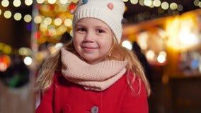 Πορτρέτο του ευτυχούς μικρού κοριτσιού στην αγορά Χριστουγέννων φιλμ μικρού μήκους