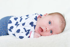 Πορτρέτο του ευτυχούς μπλε-eyed κοριτσάκι (1 μήνας) που βρίσκεται στην κοιλιά στοκ εικόνες