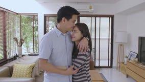 Πορτρέτο του ευτυχούς νέου ασιατικού ζεύγους στο σπίτι το άτομο εκφράζει τις συγκινήσεις του και φιλά τη σύζυγό του φιλμ μικρού μήκους
