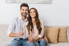πορτρέτο του ευτυχούς νέου ζεύγους με τα ποτήρια της σαμπάνιας που στηρίζονται στον καναπέ στοκ εικόνα με δικαίωμα ελεύθερης χρήσης