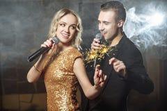 Πορτρέτο του ευτυχούς νέου ζεύγους με τα sparklers που τραγουδά με το μικρόφωνο στοκ φωτογραφία