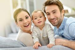 Πορτρέτο του ευτυχούς νέου ζεύγους με το μωρό στον καναπέ στοκ φωτογραφία