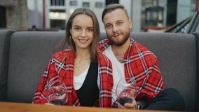 Πορτρέτο του ευτυχούς νέου ζεύγους που χαμογελά στη κάμερα Γυαλιά με το κρασί honeymoon φιλμ μικρού μήκους