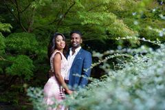 Πορτρέτο του ευτυχούς νέου ζεύγους σε έναν κήπο με το όμορφο φύλλωμα στοκ φωτογραφία με δικαίωμα ελεύθερης χρήσης