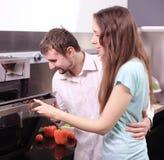 Πορτρέτο του ευτυχούς νέου μαγειρέματος ζευγών μαζί στην κουζίνα Στοκ Φωτογραφίες