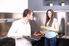 Πορτρέτο του ευτυχούς νέου μαγειρέματος ζευγών μαζί στην κουζίνα Στοκ Φωτογραφία
