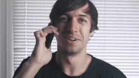 Πορτρέτο του ευτυχούς νεαρού άνδρα που μιλά στο τηλέφωνο και που χαμογελά στο υπόβαθρο των τυφλών απόθεμα βίντεο