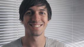 Πορτρέτο του ευτυχούς νεαρού άνδρα που χαμογελά στα πλαίσια των τυφλών γραφείων απόθεμα βίντεο