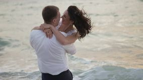 Πορτρέτο του ευτυχούς συναισθηματικού ζεύγους των όμορφων newlyweds που αγκαλιάζουν tenderly στο υπόβαθρο της θάλασσας κατά τη δι απόθεμα βίντεο