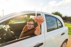 Πορτρέτο του ευτυχούς χαμογελώντας νεαρού άνδρα, της συνεδρίασης αγοραστών στο νέο αυτοκίνητό του και της παρουσίασης κλειδιών έξ Στοκ εικόνες με δικαίωμα ελεύθερης χρήσης