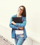 Πορτρέτο του ευτυχούς χαμογελώντας κοριτσιού σπουδαστών στα γυαλιά με το φάκελλο στοκ εικόνες
