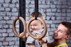 Πορτρέτο του ευτυχούς χαμογελώντας πατέρα και λίγου γιου που ασκούν με τα gimnastic δαχτυλίδια ενάντια στο τουβλότοιχο στη γυμνασ Στοκ εικόνα με δικαίωμα ελεύθερης χρήσης