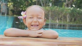 Πορτρέτο του ευτυχούς χαμόγελου κοριτσιών παιδιών στην άκρη της πισίνας σε σε αργή κίνηση απόθεμα βίντεο