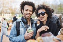 Πορτρέτο του ευτυχούς χαριτωμένου σκοτεινός-ξεφλουδισμένου ζεύγους με το afro hairstyle, strolling στο φεστιβάλ τροφίμων, τη δοκι στοκ εικόνα