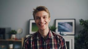 Πορτρέτο του ευτυχούς όμορφου τύπου στο καθιερώνον τη μόδα ελεγμένο πουκάμισο που χαμογελά και που εξετάζει τη κάμερα που στέκετα απόθεμα βίντεο