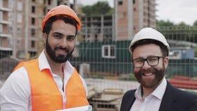 Πορτρέτο του ευτυχών οικοδόμου και του επιχειρηματία που εξετάζουν τη κάμερα που στέκεται στο υπόβαθρο εργοτάξιων οικοδομής απόθεμα βίντεο