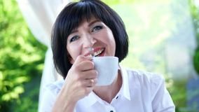 Πορτρέτο του ευχάριστου χαμόγελου, ευτυχής όμορφη πραγματική χρονών ουκρανική γυναίκα 40 μια γυναίκα πίνει το τσάι χωρίς να πάρει απόθεμα βίντεο