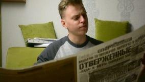 Πορτρέτο του εφήβου νεαρών άνδρων που διαβάζει την πολύ μεγάλη παλαιά εφημερίδα στα ρωσικά απόθεμα βίντεο