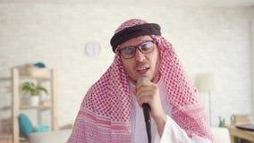 Πορτρέτο του εύθυμου αραβικού ατόμου στα παραδοσιακά ενδύματα που τραγουδούν στο μικρόφωνο καραόκε στο σπίτι απόθεμα βίντεο
