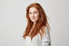 Πορτρέτο του εύθυμου ευτυχούς όμορφου κοριτσιού με το πανούργο χαμόγελο τρίχας που εξετάζει τη κάμερα πέρα από το άσπρο υπόβαθρο στοκ φωτογραφία με δικαίωμα ελεύθερης χρήσης