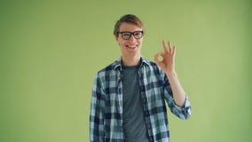 Πορτρέτο του εύθυμου νεαρού άνδρα που παρουσιάζει ΕΝΤΑΞΕΙ χειρονομία και που χαμογελά την εξέταση τη κάμερα απόθεμα βίντεο