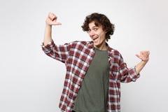 Πορτρέτο του εύθυμου νεαρού άνδρα στα περιστασιακά ενδύματα που φαίνεται κάμερα, που δείχνει τους αντίχειρες σε τον που απομονώνε στοκ φωτογραφίες με δικαίωμα ελεύθερης χρήσης