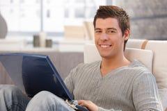 Πορτρέτο του εύθυμου νεαρού άνδρα που χρησιμοποιεί τον υπολογιστή Στοκ Εικόνες