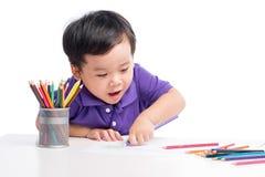 Πορτρέτο του εύθυμου σχεδίου αγοριών με τα ζωηρόχρωμα μολύβια Στοκ Φωτογραφίες
