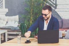 Πορτρέτο του εύθυμου freelancer στο γραφείο στη καφετερία στοκ εικόνες