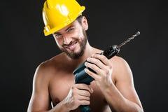 Πορτρέτο του ελκυστικού εργάτη γυμνοστήθων με το τρυπάνι στοκ φωτογραφίες