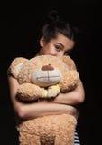 Πορτρέτο του ελκυστικού καυκάσιου brunette γυναικών χαμόγελου με την αρκούδα στο μαύρο πυροβολισμό στούντιο Στοκ Εικόνες