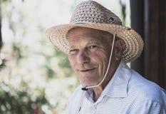 Πορτρέτο του ηλικιωμένου χαμογελώντας ατόμου με το καπέλο αχύρου που εξετάζει το έκκεντρο στοκ εικόνες με δικαίωμα ελεύθερης χρήσης