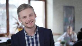 Πορτρέτο του δημιουργικού επιτυχούς έναρξη-ανωτέρου που λειτουργεί στο πολυάσχολο γραφείο Κοιτάζει στη κάμερα και χαμογελά απόθεμα βίντεο