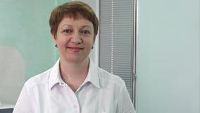 Πορτρέτο του ηλικίας θηλυκού γιατρού στο διάδρομο νοσοκομείων που εξετάζει το χαμόγελο καμερών απόθεμα βίντεο