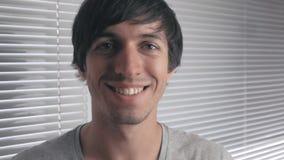 Πορτρέτο του θετικού νεαρού άνδρα που χαμογελά στα πλαίσια των τυφλών γραφείων απόθεμα βίντεο