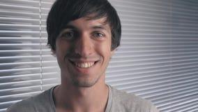 Πορτρέτο του θετικού νεαρού άνδρα που χαμογελά στο υπόβαθρο των τυφλών γραφείων απόθεμα βίντεο