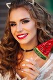 Πορτρέτο του θετικού προκλητικού brunette με τα κόκκινα χείλια που κρατά την καραμέλα Στοκ φωτογραφία με δικαίωμα ελεύθερης χρήσης