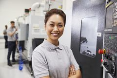 Πορτρέτο του θηλυκού μηχανικού που ενεργοποιεί CNC τα μηχανήματα στο εργοστάσιο στοκ εικόνα με δικαίωμα ελεύθερης χρήσης