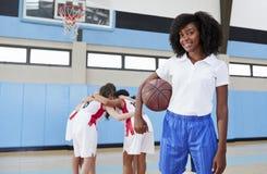 Πορτρέτο του θηλυκού προπονητής του μπάσκετ γυμνασίου με τη συσσώρευση ομάδας στο υπόβαθρο στοκ φωτογραφίες