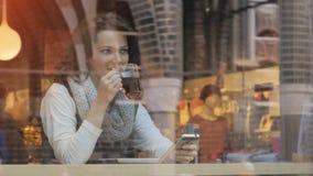 Πορτρέτο του θηλυκού τσαγιού κατανάλωσης και κοίταγμα από την προθήκη καφέ Στοκ φωτογραφίες με δικαίωμα ελεύθερης χρήσης