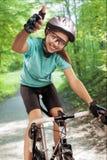 Πορτρέτο του θηλυκού αναβάτη ποδηλάτων εξωτερικού και που παρουσιάζει thumbsup. comp Στοκ Εικόνες