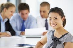 Πορτρέτο του θηλυκού ανώτερου υπαλλήλου με τη συνεδρίαση των γραφείων στο υπόβαθρο Στοκ Φωτογραφία