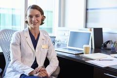 Πορτρέτο του θηλυκού γιατρού που φορά το άσπρο παλτό στην αρχή Στοκ Φωτογραφίες