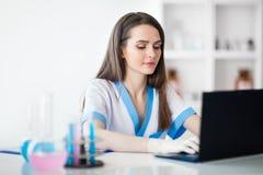 Πορτρέτο του θηλυκού επιστήμονα που εργάζεται στο lap-top στη χημική εργασία στοκ φωτογραφία