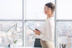 Πορτρέτο του θηλυκού διευθυντή γραφείων στη φθορά του κομψού φορέματος, χρησιμοποίηση του υπολογιστή ταμπλετών της, στάση κοντά σ στοκ φωτογραφία με δικαίωμα ελεύθερης χρήσης