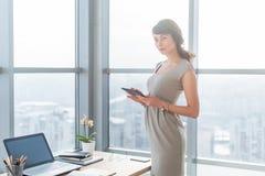 Πορτρέτο του θηλυκού διευθυντή γραφείων στη φθορά του κομψού φορέματος, χρησιμοποίηση του υπολογιστή ταμπλετών της, στάση κοντά σ στοκ φωτογραφίες με δικαίωμα ελεύθερης χρήσης