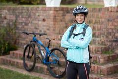 Πορτρέτο του θηλυκού ποδηλάτη που στέκεται με τα όπλα που διασχίζονται Στοκ φωτογραφία με δικαίωμα ελεύθερης χρήσης